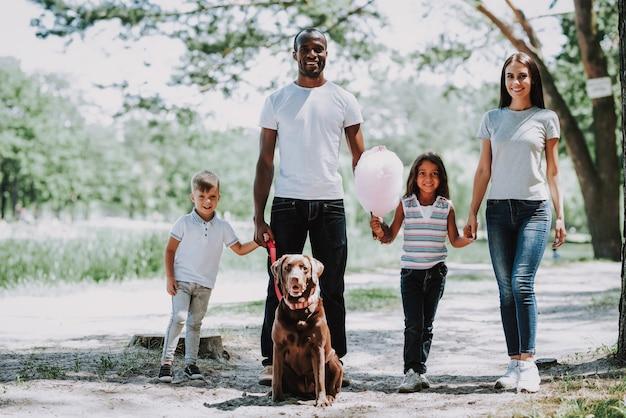 O paizinho africano e a mamã caucasiano caçoam a caminhada pelo parque. Foto Premium