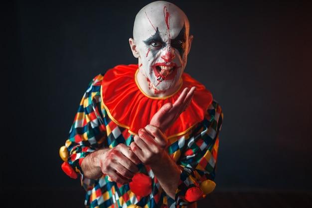 O palhaço louco e sangrento segura a mão humana, o dedo entre os dentes. homem maquiado com fantasia de halloween, louco maníaco Foto Premium