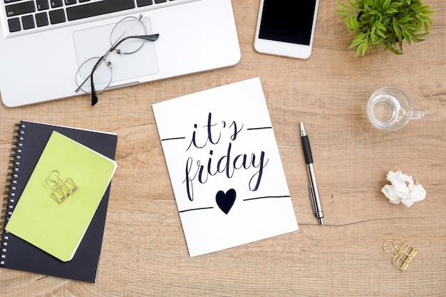 O papel com é caligrafia do texto de sexta-feira está no meio da tabela de madeira da mesa de escritório com fontes. vista superior, lay plana. Foto Premium