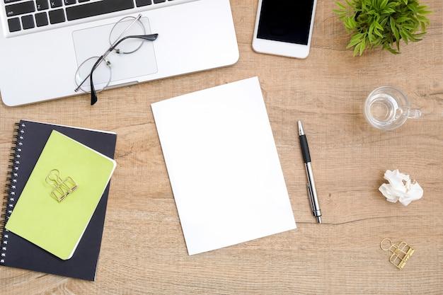 O papel em branco está sobre a tabela de madeira da mesa de escritório. Foto Premium
