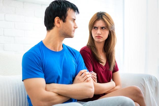 O par da família que senta-se no sofá que não fala após o argumento, marido novo está cansado da mulher ofendida brigando constante virou de volta ao noivo com os braços transversalmente. Foto Premium