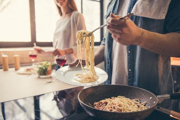 O par está sorrindo ao cozinhar na cozinha. Foto Premium