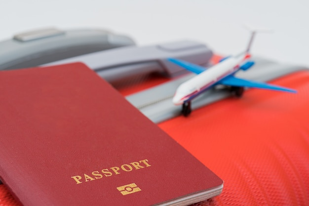 O passaporte vermelho e o modelo do avião encontram-se na mala vermelha. Foto Premium
