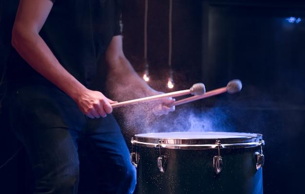 O percussionista toca com paus no chão e sob a iluminação do estúdio. conceito de concerto e performance. Foto gratuita