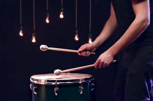 O percussionista toca paus no chão em uma sala escura e com bela iluminação. conceito de concerto e performance. Foto Premium