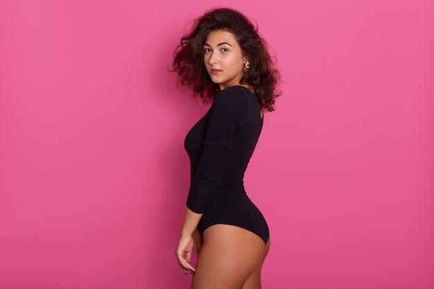 O perfil da jovem mulher veste combidress preto, posando isolado na menina cor-de-rosa, encantadora, tendo cabelos ondulados escuros e brincos elegantes, fêmea atraente. Foto gratuita