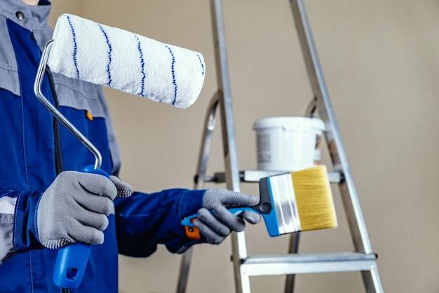 O pintor de gesso está pronto para pintar a parede. nas mãos de um rolo e um pincel. uma escada e um balde de tinta ao fundo. Foto Premium