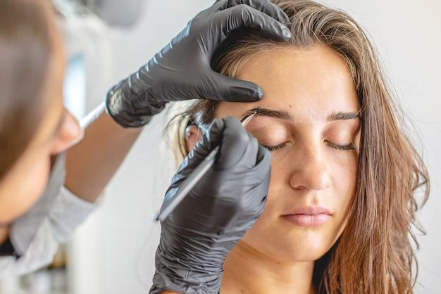 O pintor de sobrancelhas mestre de beleza pinta as sobrancelhas colorindo-as com hena. mulher que trabalha em luvas pretas. arquitetura de sobrancelha Foto Premium