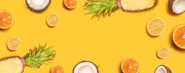 O plano da fruta tropical coloca com abacaxi, laranjas, limão e coco em um fundo pastel. Foto Premium