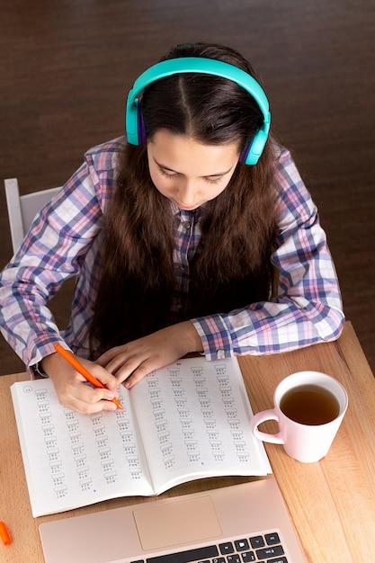O portátil do estudante que faz a anotação, fones de ouvido de escuta da música e livro de leitura, bebe o café. conceito elearning. Foto Premium