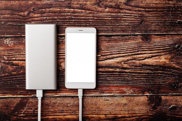 O powerbank cobra um smartphone em um fundo de madeira. bateria externa universal para gadgets espaço livre e composição minimalista. Foto Premium