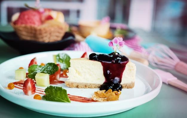 O prato de bolo de queijo de mirtilo colocar na mesa, luz embaçada em torno de Foto Premium