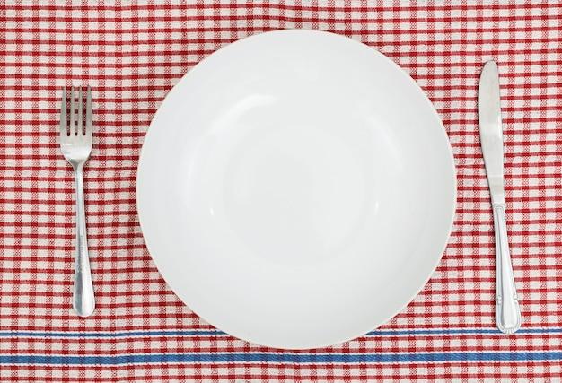 O prato vazio com folk e faca na mesa vermelha. Foto Premium