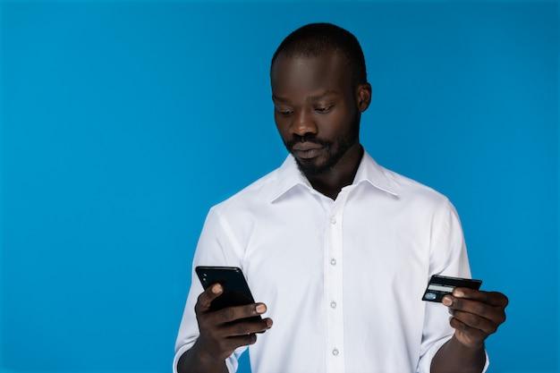 O primeiro plano afro-americano barbudo pensativo está olhando para o celular e segurando o cartão de crédito Foto gratuita
