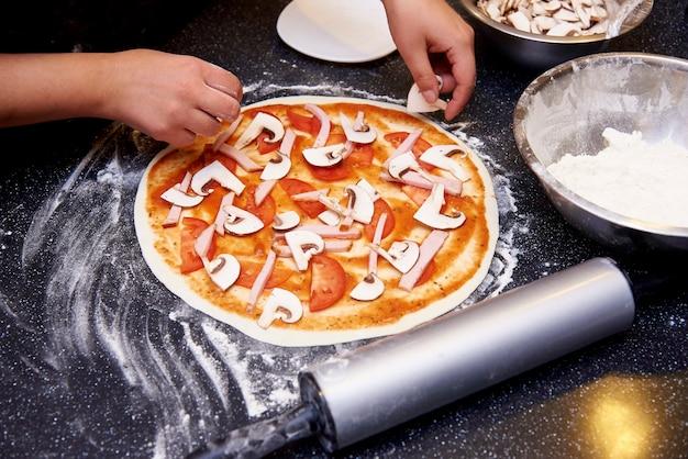 O processo de cozinhar pizza com carne, cogumelos, tomate e queijo. Foto Premium