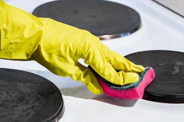 O processo de lavar um fogão elétrico. uma mão em uma luva amarela limpa a superfície branca da sujeira. Foto Premium