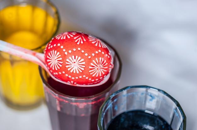 O processo de pintar ovos de páscoa com corante alimentar e cera derretida. Foto Premium