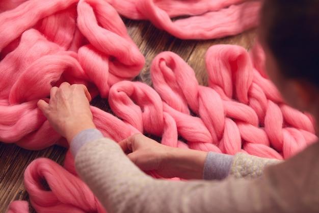 O processo de tricotar cobertores feitos de merino. Foto Premium