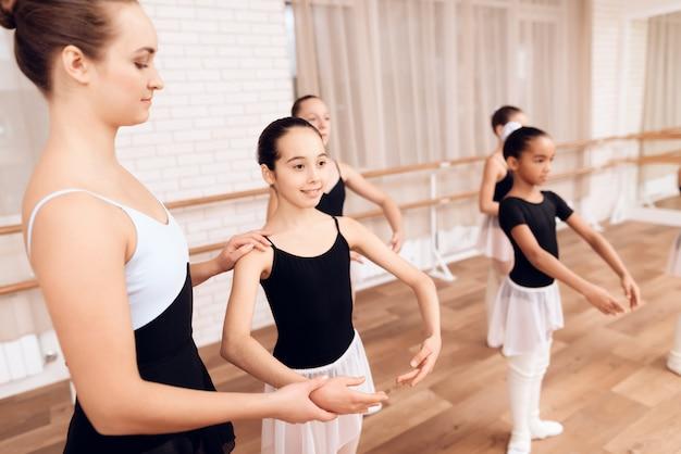 O professor novo feliz do bailado treina crianças diligentes. Foto Premium