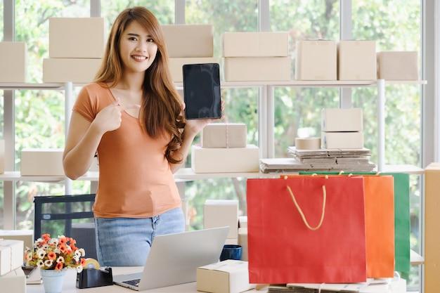 O proprietário de mulher de negócios asiáticos feliz linda jovem da pme on-line está de pé e apontando para tablet ou smartphone em seu escritório em casa inicialização com caixa de embalagem e sacolas de compras, compras on-line Foto Premium