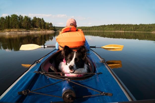 O proprietário e o cachorro em um colete salva-vidas flutuando em um barco de caiaque Foto Premium