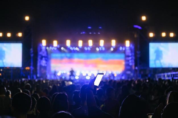 O público da juventude da silhueta está olhando o concerto da noite Foto Premium