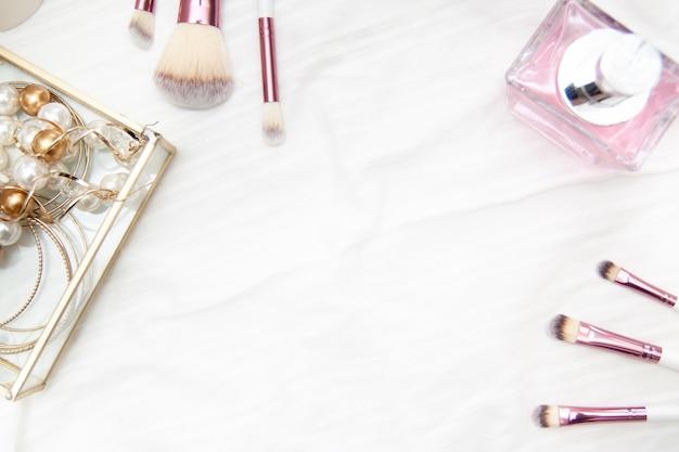 O quadro para o texto feito da composição profissional cor-de-rosa escova grânulos e brincos do perfume na caixa no fundo branco. Foto Premium
