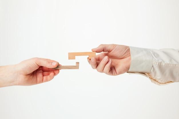 O quebra-cabeça de madeira do brinquedo nas mãos solated no fundo branco Foto gratuita
