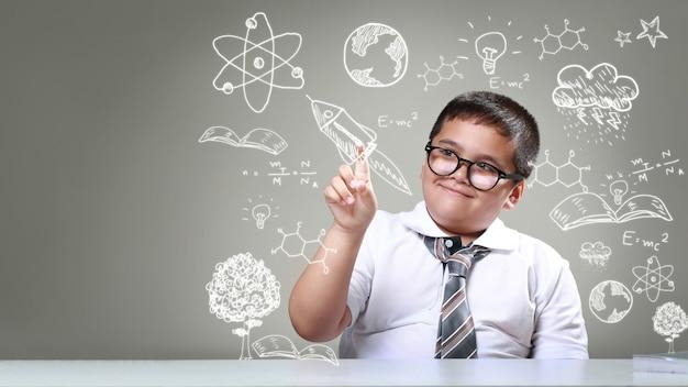 O rapaz apontando para desenhos de ciência Foto Premium