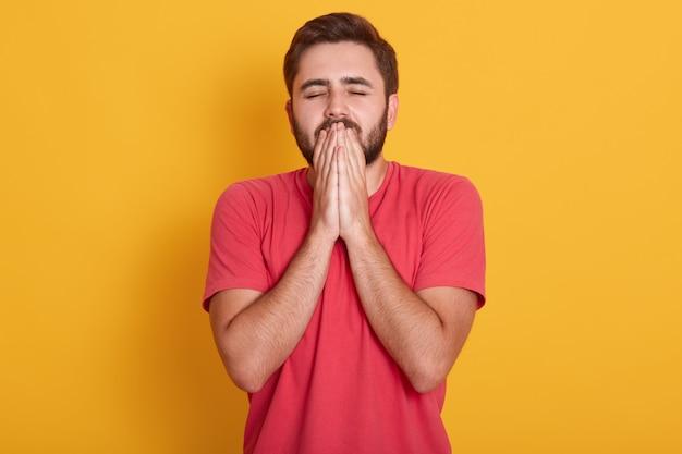 O rapaz bonito jovem de estúdio com olhos fechados espera por fortuna e boa sorte, carrinhos vestindo camiseta casual vermelha, mantém as mãos em gesto de oração, isolado no amarelo. Foto gratuita
