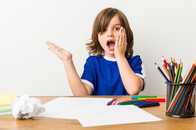 O rapaz pequeno que pinta e que faz trabalhos de casa em sua mesa guarda o espaço da cópia em uma palma. Foto Premium