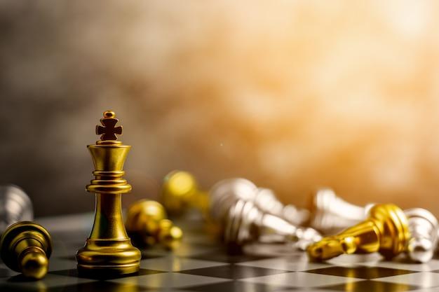O rei de ouro do xadrez em pé encontra derrotar os inimigos. Foto Premium