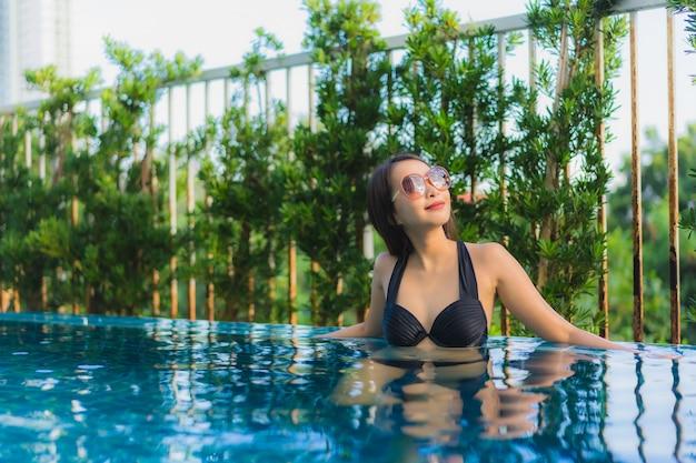O retrato as mulheres asiáticas novas bonitas sorri feliz relaxa a piscina ao ar livre no recurso Foto gratuita