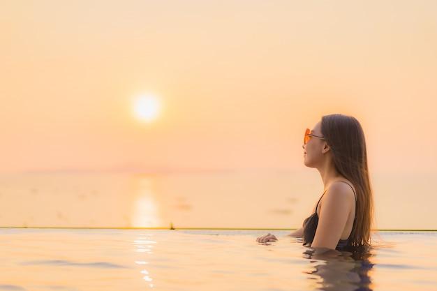 O retrato as mulheres asiáticas novas bonitas sorri feliz relaxa a piscina exterior no hotel Foto gratuita