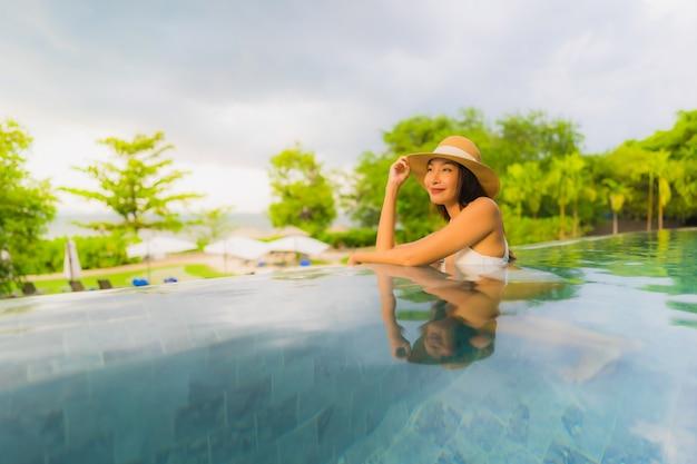 O retrato as mulheres asiáticas novas bonitas sorri feliz relaxa em torno da piscina exterior no hotel Foto gratuita