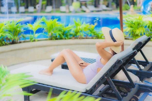 O retrato as mulheres asiáticas novas bonitas sorri feliz relaxa em torno da piscina exterior Foto gratuita