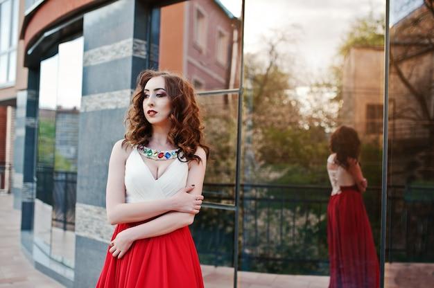 O retrato da menina na moda no vestido vermelho levantou a janela do espelho de fundo do edifício moderno Foto Premium