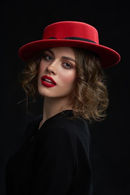 O retrato da moça bonita, batendo o batom vermelho, dia compõe e chapéu vermelho elegante. Foto Premium