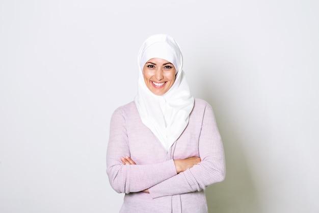 O retrato da mulher muçulmana árabe consideravelmente nova no lenço principal sorri. Foto Premium