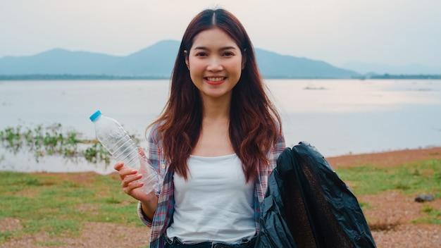 O retrato de jovens voluntárias da ásia ajuda a manter a natureza limpa, segurando resíduos de garrafas plásticas e sacos de lixo pretos na praia. conceito sobre problemas de poluição de conservação ambiental. Foto gratuita
