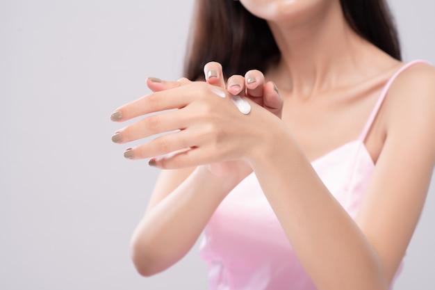 O retrato de mulheres asiáticas usa a loção para o corpo em seus braços. conceito de cuidados com a pele. Foto Premium