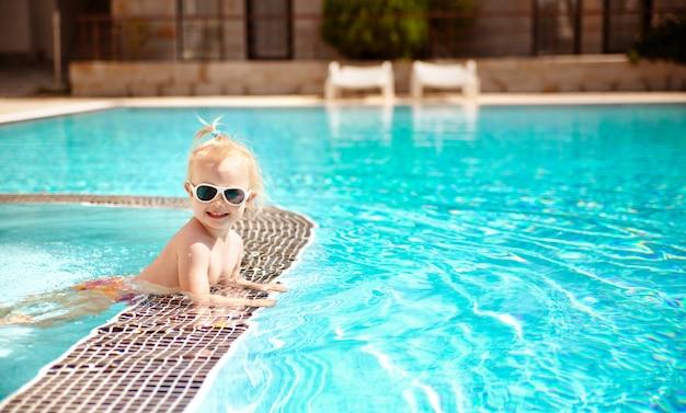 O retrato de um bebê bonito louro nos óculos de sol, nadando na associação em férias de verão. Foto Premium