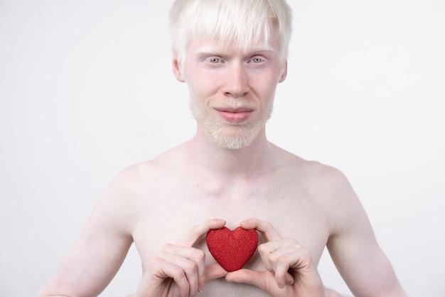 O retrato de um homem do albino no estúdio vestiu o t-shirt isolado em um fundo branco. desvios anormais. aparência incomum. anormalidade da pele Foto Premium