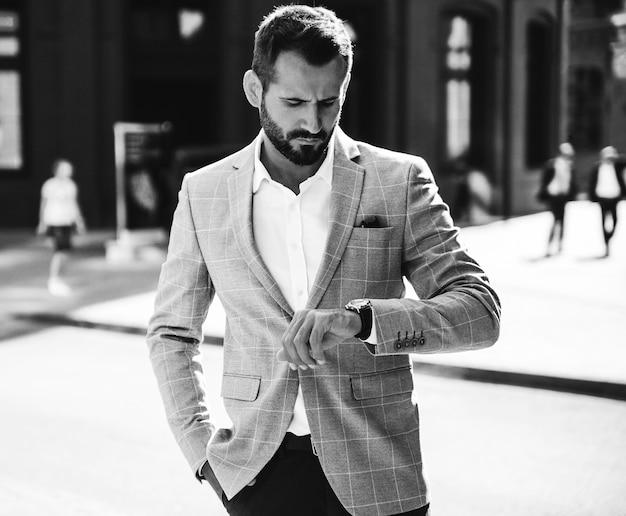 O retrato do modelo considerável do homem de negócios da forma vestiu-se no elegante terno azul. homem posando na rua fundo. metrosexual Foto gratuita