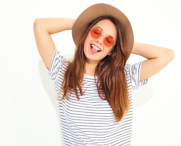 O retrato do modelo de mulher de riso à moda novo no verão ocasional veste-se no chapéu marrom com a composição natural isolada na parede branca. Foto gratuita