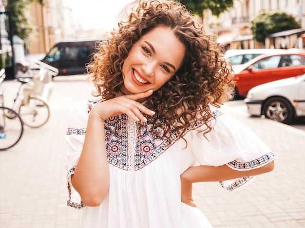 O retrato do modelo de sorriso bonito com o penteado afro das ondas vestiu-se no vestido branco do moderno do verão. Foto gratuita