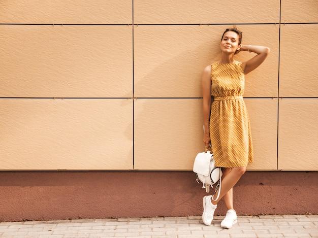 O retrato do modelo de sorriso bonito do moderno vestiu-se no vestido amarelo do verão. menina na moda posando na rua. mulher engraçada e positiva se divertindo Foto gratuita