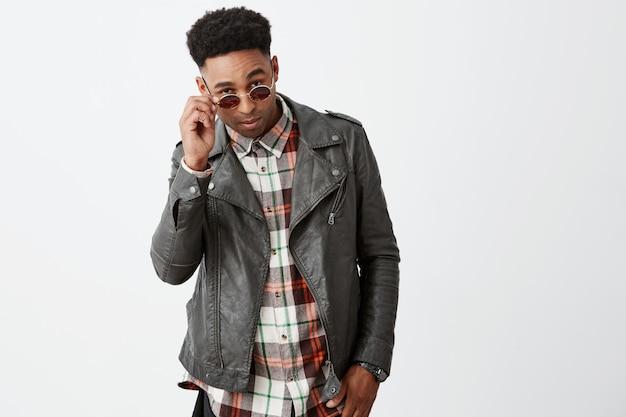 O retrato do modelo masculino africano novo atrativo escuro de pele escura com cabelo encaracolado em couro preto outwear decolando óculos de sol com a mão com expressão fresca e calma. Foto gratuita
