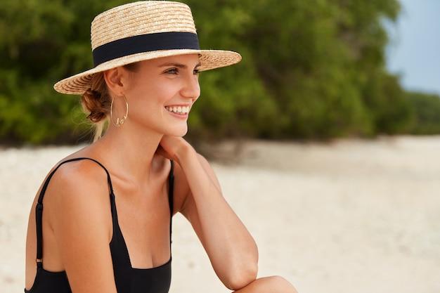 O retrato lateral de uma mulher sonhadora feliz olha para o oceano enquanto se senta em uma praia tropical, usa chapéu de verão, tem o cabelo amarrado, tem harmonia e relaxamento. mulher usa biquíni e admira vista do mar Foto gratuita