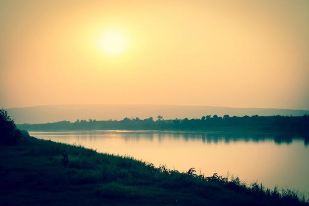 O rio e as montanhas ao pôr do sol Foto Premium
